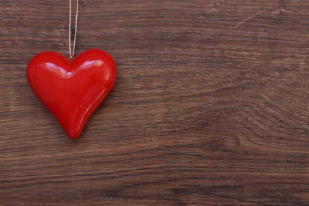 Beautiful red heart hanging on string over wooden background. Valentines day card.