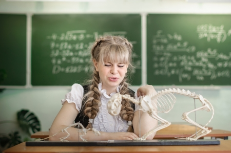 Schoolgirl and the skeleton of an animal on the biology photo