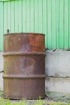 ply: Rusty ply barrel on the background of green cement blocks and boards Stock Photo
