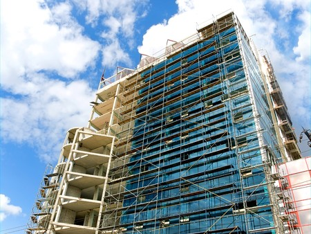 high building of glass and concrete on a blue sky background.  under construction photo