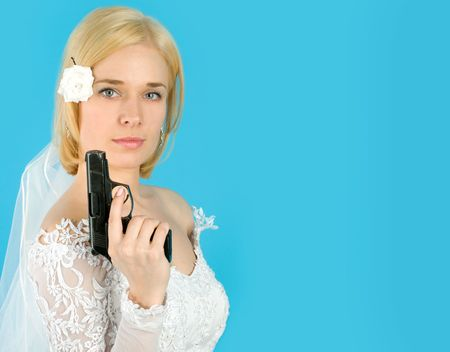 Pretty bride with gun isolated on blue photo