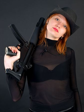 Sexy red young woman in a cowboy hat holding the gun photo