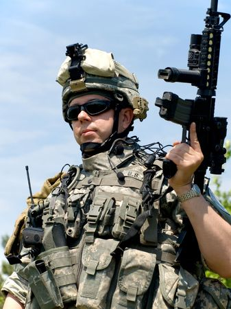 US soldier in camouflage uniform with his rifle Stock Photo