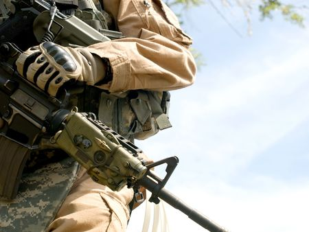 US soldier in camouflage uniform holding his rifle Stock Photo
