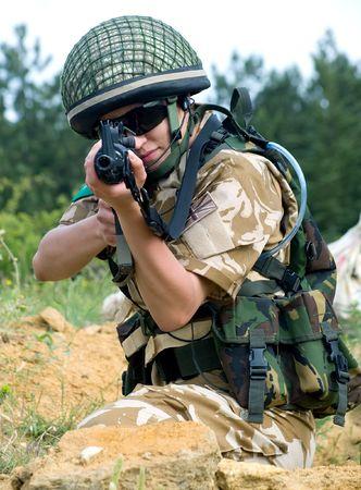 british army: British girl soldier in desert uniform aiming her rifle