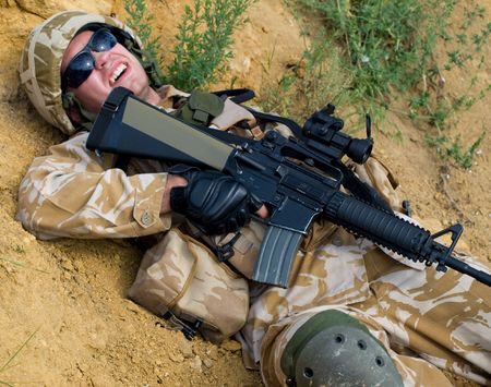 wounded: British soldier in desert uniform lying wounded Stock Photo