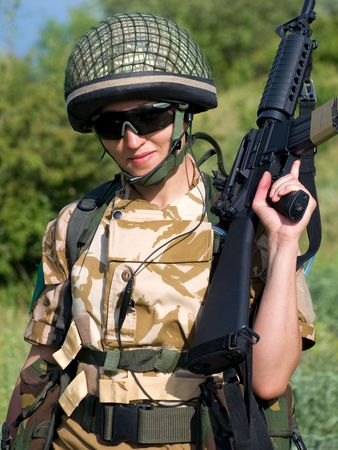 acu: British girl soldier in desert uniform holding her rifle Stock Photo