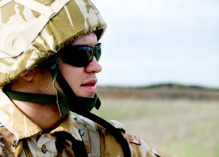 British soldier with the reflection of UK flag in glasses looking forward photo