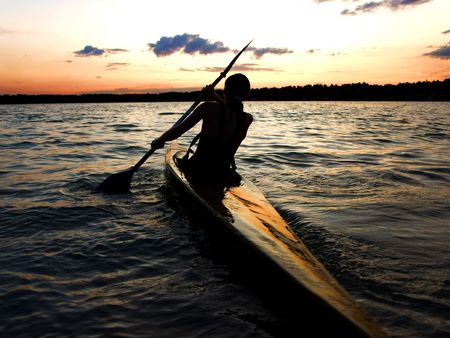 canoeist: A female kayaker paddles across a lake against sunset Stock Photo