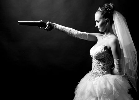 beauty young bride in white dress holding the old gun photo