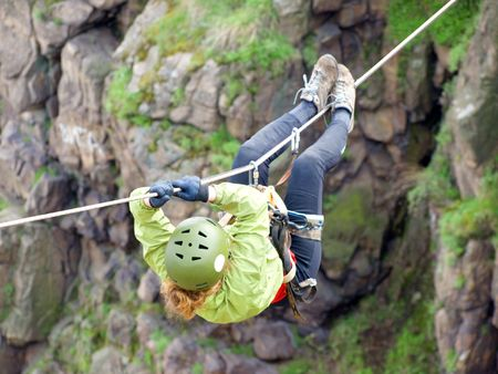 traverse: A female climber crosses a gorge along a tyrolean traverse Stock Photo