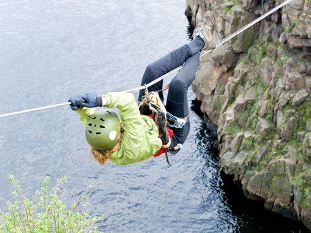 A female climber crosses a gorge along a tyrolean traverse Stock Photo