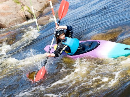 a shot of the female kayaker on the rough water
