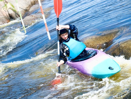 kayaker: a shot of the female kayaker on the rough water