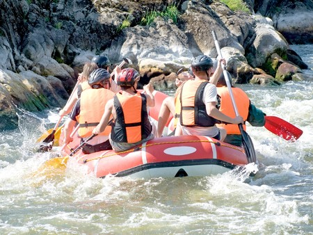 group of people in a rafting boat, rowing on the river