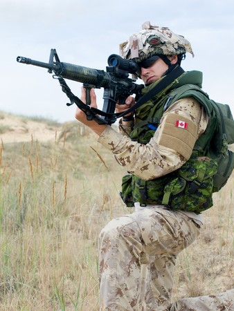 assault forces: soldier in desert uniform aiming his rifle Stock Photo