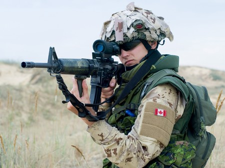 canadian: soldier in desert uniform aiming his rifle Stock Photo
