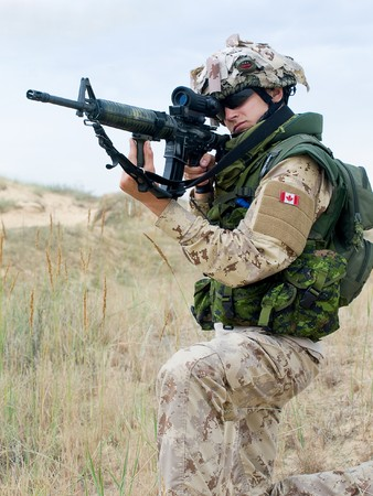 canadian military: soldier in desert uniform aiming his rifle Stock Photo