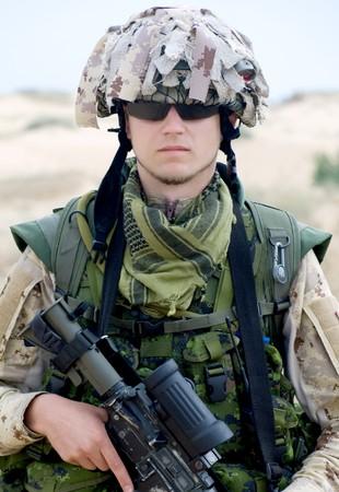 soldier in desert uniform holding his rifle photo