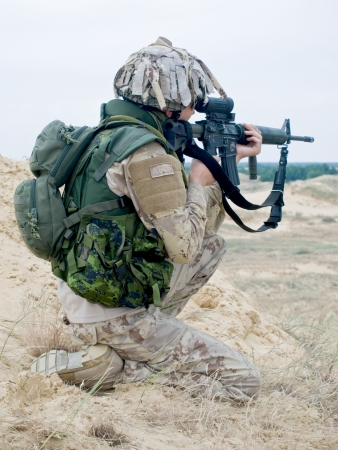 iraq war: soldier in desert uniform aiming his rifle Stock Photo