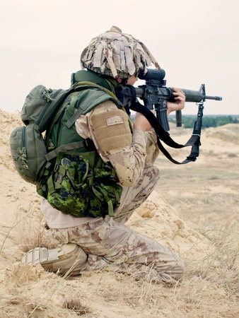 soldier in desert uniform aiming his rifle photo