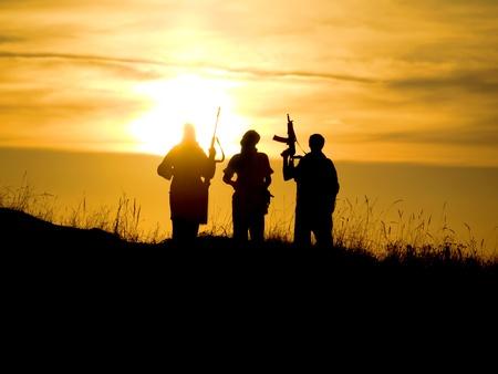 silhouette soldat: Silhouettes de plusieurs soldats avec des fusils contre un coucher de soleil Banque d'images