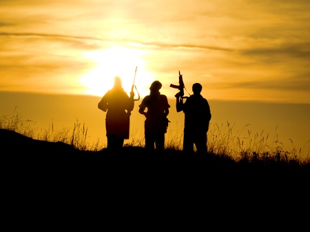 Silhouettes of several soldiers with rifles against a sunset
