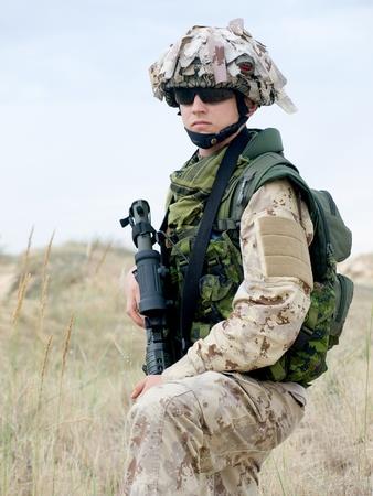 soldado en desierto uniforme con su rifle