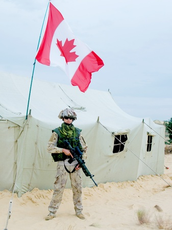 bivouac: canadian soldier in desert uniform near the army tent