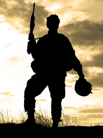 war and military: Silhouette of US soldier with rifle against a sunset Stock Photo