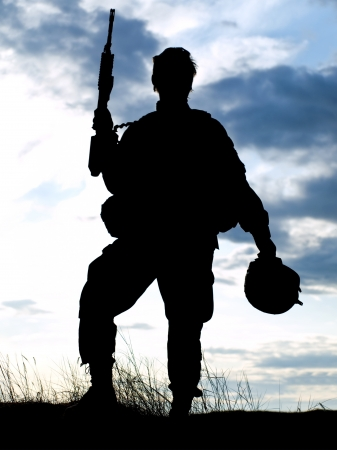 acu: Silhouette of US soldier with rifle against a sunset Stock Photo