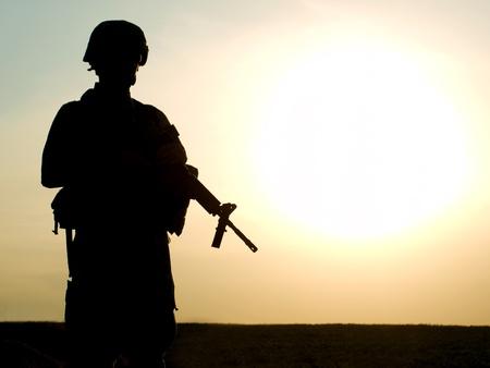 silhouette soldat: Silhouette de soldat américain avec le fusil contre un coucher de soleil