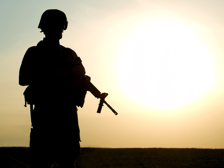american soldier: Silhouette of US soldier with rifle against a sunset Stock Photo