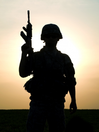 army soldier: Silhouette of US soldier with rifle against a sunset Stock Photo