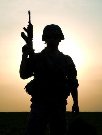 soldado: Silueta de soldado estadounidense con fusil contra una puesta de sol