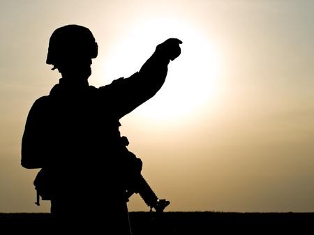 guerra: Silueta de soldado de EE.UU. con el rifle en contra de una puesta de sol