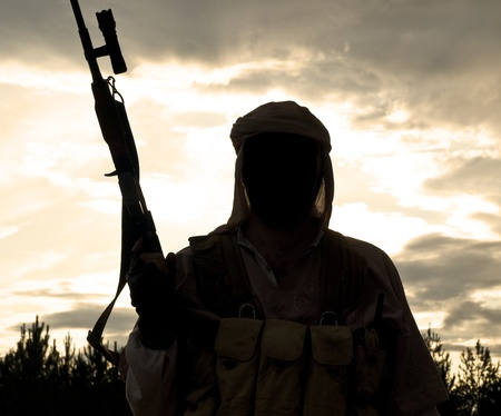 militant: Silhouette of muslim militant with rifle