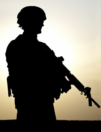 armed services: Silhouette of US soldier with rifle against a sunset Stock Photo
