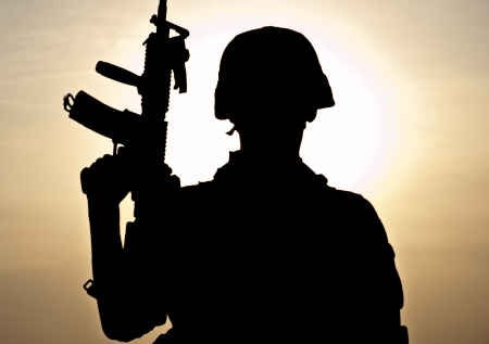 american soldier: Silhouette of young soldier against the sun