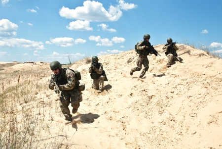 commando: Squad of soldiers run through the desert through the military operation