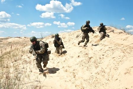 Trupp Soldaten durch die Wüste über die militärische Operation ausführen Standard-Bild - 17099184