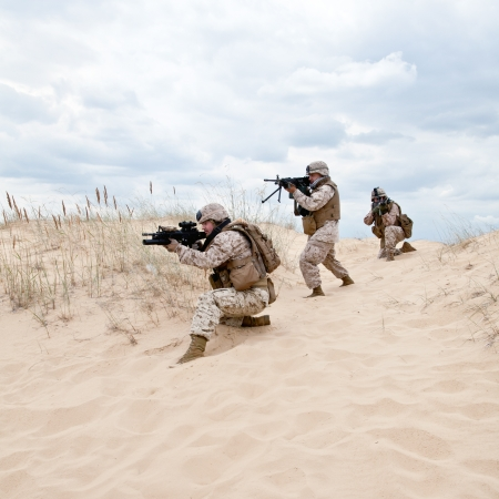 american soldier: US marines run through the desert through the military operation Stock Photo