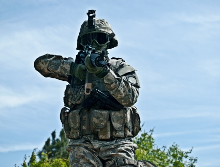 assault forces: Attacking US soldier shooting his gun moving towards the camera Stock Photo