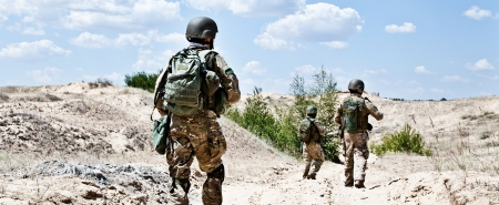 patrolling: Squad of soldiers patrolling across the desert Stock Photo