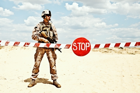 US marine with assault rifle near the barrier at a checkpoint