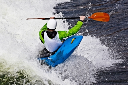 kayak: an active male kayaker rolling and surfing in rough water