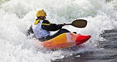 whitewater: an active male kayaker rolling and surfing in rough water