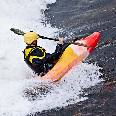 extreme danger: an active male kayaker rolling and surfing in rough water