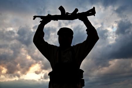 Silhouette der muslimischen Militanten mit Gewehr Standard-Bild - 20041556