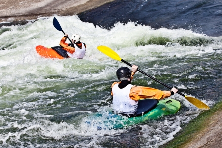 two active kayakers are rolling and surfing in rough water Stock Photo
